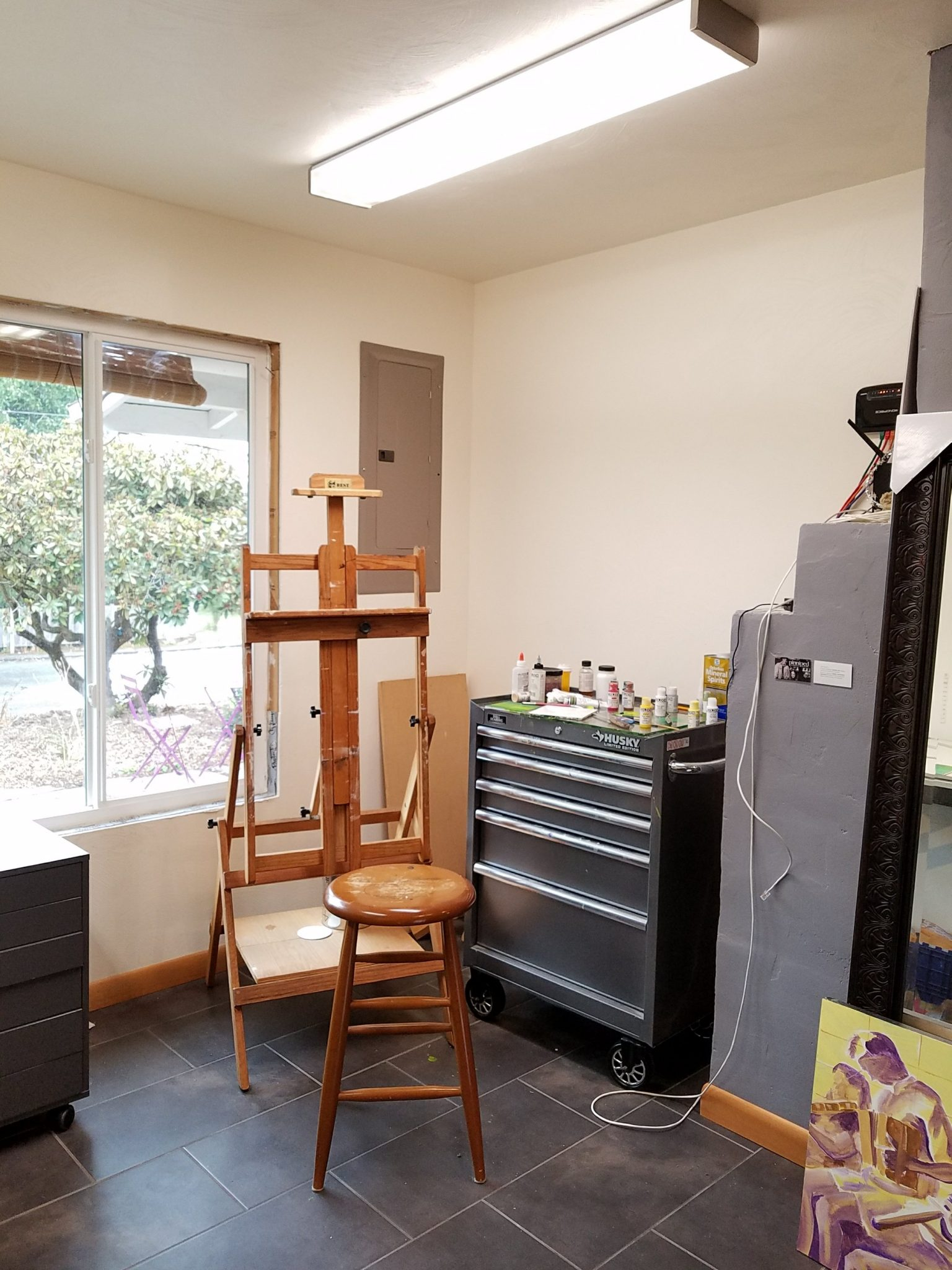 Photo of an artist's wooden easel, stool, and a large tool chest.