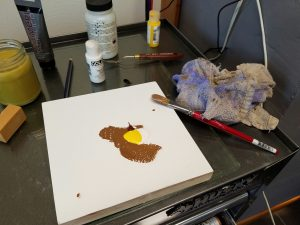 a gessoed panel with globs of unmixed brown, yellow, and white paint on it, brush and paint tubes in the background.