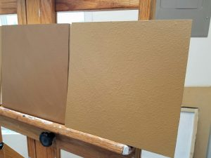 two square brown painting panels on an easel. The one on the right has a slightly lumpy texture.