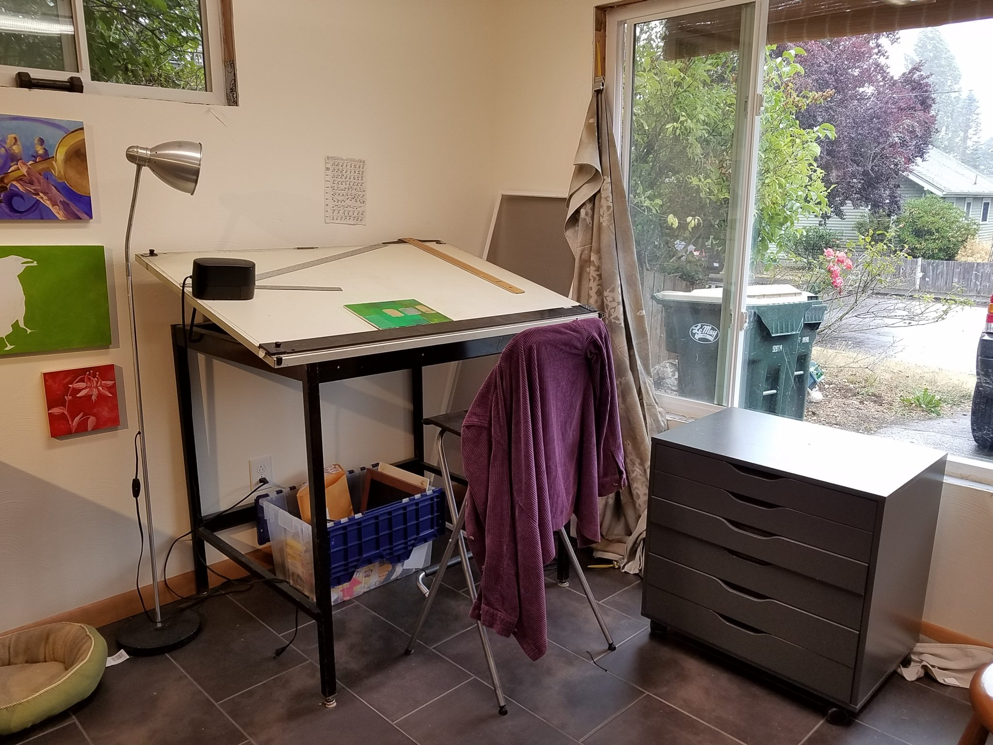 A picture of a room with a large metal drafting table in the corner and a smaller wheeled chest of drawers under a window.